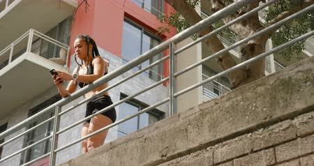 zábradlí : Low angle view of young African American woman using mobile phone in the city. She is standing on a bridge 4k Dostupné videozáznamy