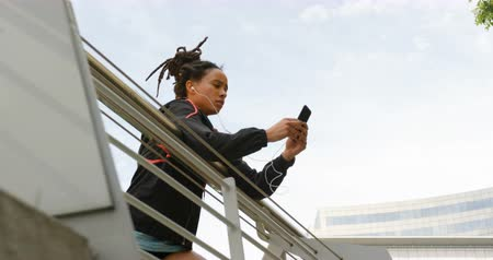 baixo ângulo : Low angle view of young African American woman using mobile phone in the city. She is standing on a bridge 4k Stock Footage