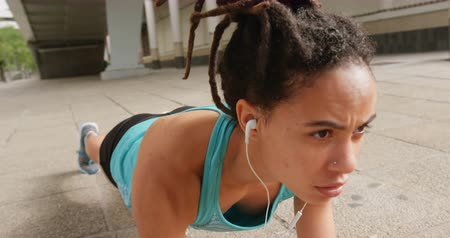 vyvažování : Front view of young African American woman exercising in the city. She is listening music on earphones 4k