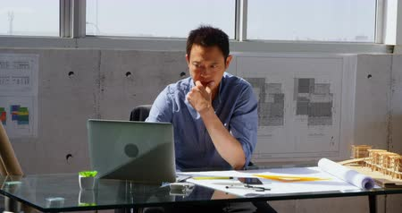 grasduinen : Front view of Asian male architect using laptop on desk in a modern office. He is sitting at desk 4k