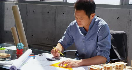 geometry compass : Front view of Asian male architect working on blueprint at desk in a modern office. He is using set square and calculator 4k Stock Footage