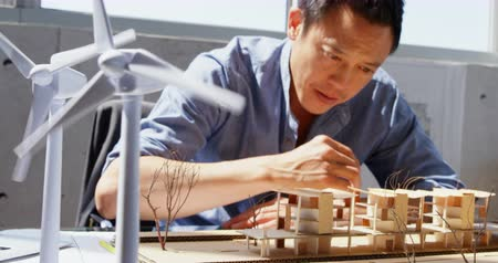 fele olyan hosszú : Front view of Asian male architect looking at architectural model in a modern office. He is sitting at desk 4k