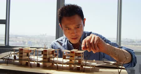 felülnézet : Front view of Asian male architect looking at architectural model in a modern office. He is standing at desk 4k