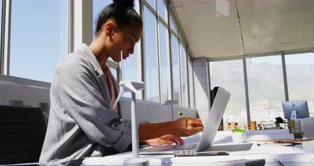 Хорошо одетый : Side view of African American Businesswoman using laptop at desk in a modern office. Windmill and architectural model on a table 4k
