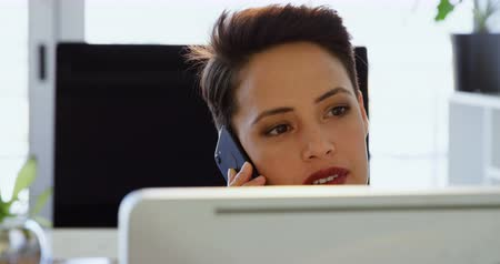 fare : Front view of Caucasian Businesswoman talking on mobile phone at desk in a modern office. She is working on computer 4k