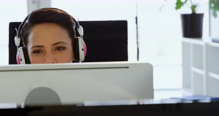 myszka komputerowa : Front view of Caucasian Businesswoman in headphones working on computer at desk in office. She is sitting at desk 4k