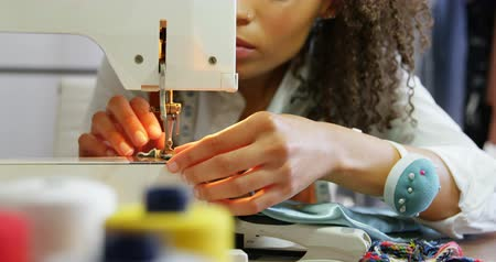 stiksel : Front view of African American female fashion designer working with sewing machine in workshop. She is putting thread in the sewing machine 4k