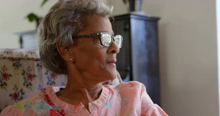 rifugio : Front view of Caucasian senior woman relaxing at nursing home. She is looking away 4k