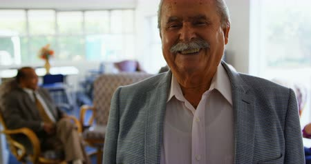 fele olyan hosszú : Front view of Happy Asian senior man standing in nursing home. Senior friends interacting with each other in the background 4k