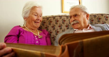 together trust : Front view of active Caucasian senior couple looking at photo album in nursing home. They are smiling 4k