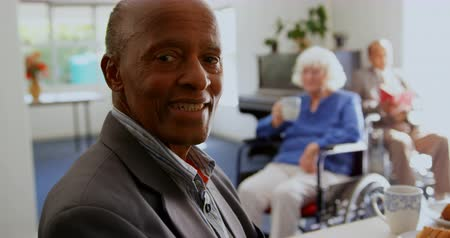 abrigo : Side view of African American senior man smiling in nursing home. He is smiling and looking at camera 4k Vídeos