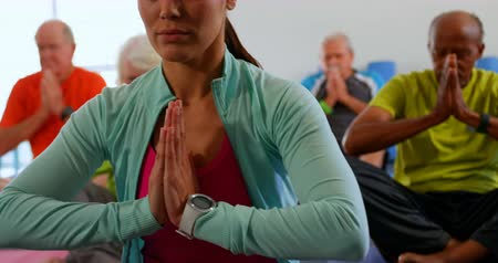 mulheres adultas meados : Front view of active mixed-race senior people with trainer performing yoga in fitness studio. They are meditating together 4k Vídeos