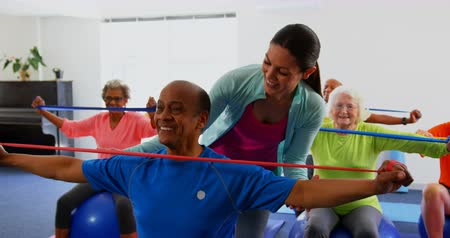пенсионер : Front view of Caucasian female trainer training senior man in exercise at fitness studio. They are exercising with resistance band 4k Стоковые видеозаписи