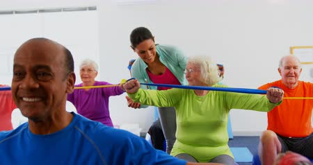 szállás : Front view of Caucasian female trainer training senior woman in exercise at fitness studio. They are exercising with resistance band 4k