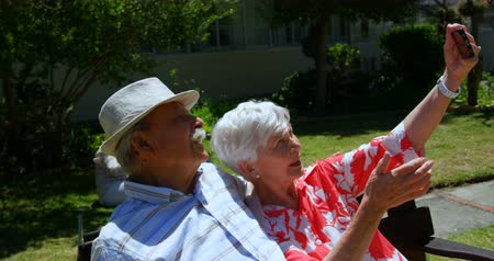 пенсионер : Front view of active Caucasian senior couple taking selfie with mobile phone in the garden of nursing home. They are sitting on a bench 4k Стоковые видеозаписи