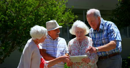 пенсионер : Group of Caucasian senior couples discussing over digital tablet in the garden of nursing home. They are standing in the garden 4k