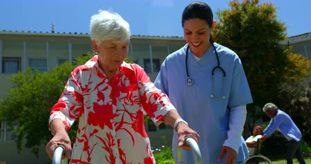 nursing : Front view of Caucasian female doctor helping senior patient to walk with walker in the garden of nursing home. Senior people in the background 4k