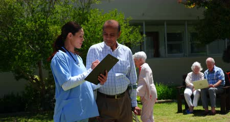 yaşlı : Front view of active Asian senior man and female doctor discussing over medical report in the garden of nursing home. They are standing together in the garden 4k