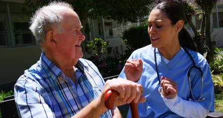 bengala : Front view of active Caucasian senior man and female doctor interacting with each other in the garden of nursing home. They are sitting on a bench 4k Stock Footage