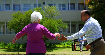 fondness : Side view of active mixed-race senior couple dancing together in the garden of nursing home. Senior man sitting on a bench in the background 4k Stock Footage