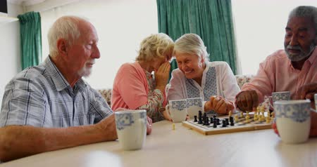 šachy : Active mixed-race senior people playing chess game in the nursing home. Senior women whispering in the background 4k