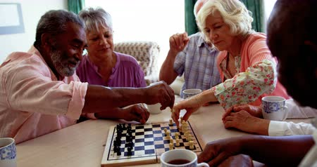 abrigo : Active mixed-race senior people playing chess game in the nursing home. They are sitting at table 4k