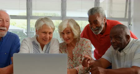 filmagens : Front view of active mixed-race senior people using laptop at nursing home. They are sitting at table 4k