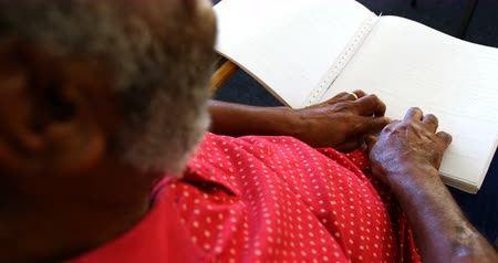 blindness : Mid section of blind senior man reading a braille book at nursing home. He is sitting on a armchair 4k