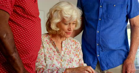 photo album : Active Caucasian senior people looking at photo album in nursing home. They are interacting with each other 4k Stock Footage