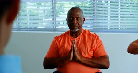 szállás : Front view of active African American senior man performing yoga in fitness studio. He is meditating 4k Stock mozgókép