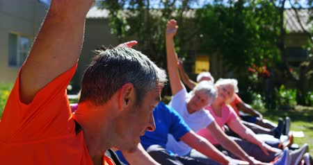 kobieta fitness : Side view of Caucasian male trainer training senior people in performing exercise at the garden of nursing home. They are exercising together 4k