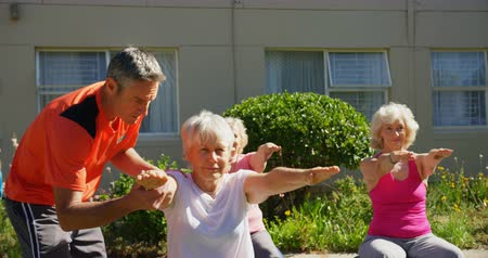 szállás : Front view of Caucasian male trainer training senior people in performing yoga at the garden of nursing home. They are exercising together 4k