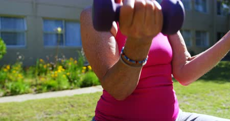 szállás : Front view of Caucasian senior people exercising with dumbbells in the garden of nursing home. She is sitting on a exercise ball 4k Stock mozgókép