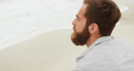 fej és vállak : Side view of Caucasian thoughtful man looking at sea on the beach. Sea surf in the background 4k Stock mozgókép