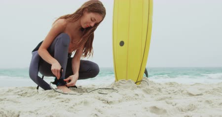 серфер : Side view of Caucasian female surfer tying surfboard leash on her leg surfboard at beach. She is getting ready for surfing 4k