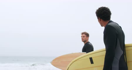 sports suit : Side view of two male surfers standing with surfboard on the beach. They are interacting with each other 4k Stock Footage