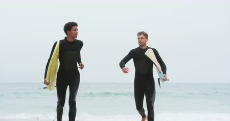 sports suit : Front view of two male surfers running together with surfboard on the beach. They are having fun 4k