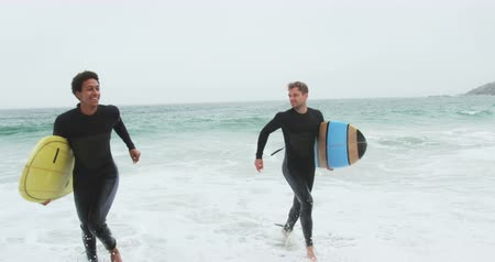 surf : Front view of two male surfers running together with surfboard on the beach. They are having fun 4k