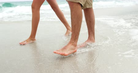 раздел : Low section of couple walking barefoot on the beach.They are spending time together 4k Стоковые видеозаписи