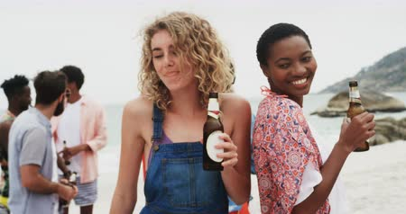 socialization : Front view of mixed-race female friends dancing together on the beach. They are drinking beer 4k