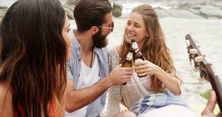 socialization : Front view of Caucasian couple toasting beer bottles on the beach. They are having fun 4k