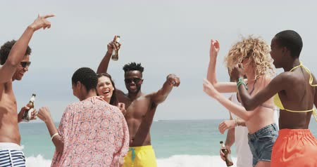 socialization : Group of mixed-race friends dancing together on the beach. They are having fun 4k