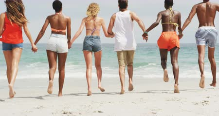 socialization : Group of mixed-race friends running together hand in hand on the beach. They are having fun 4k