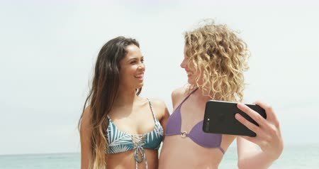fele olyan hosszú : Front view of two Mixed-race female friends taking selfie with mobile phone on the beach. They are smiling and having fun 4k Stock mozgókép