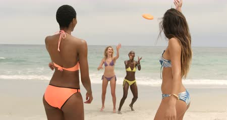 socialization : Group of mixed-race female friends playing flying disc on the beach. They are having fun 4k
