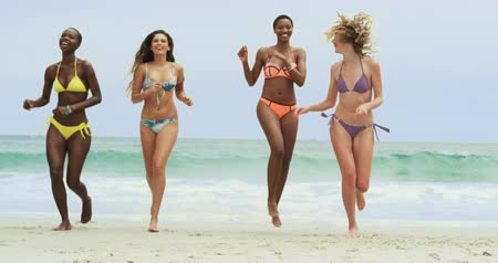 mayo : Front view of mixed-race female friends running on the beach. They are having fun 4k