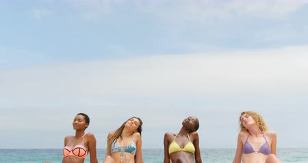 socialization : Front view of mixed-race female friends relaxing with eyes closed on the beach. Calm sea and beautiful sky in the background 4k