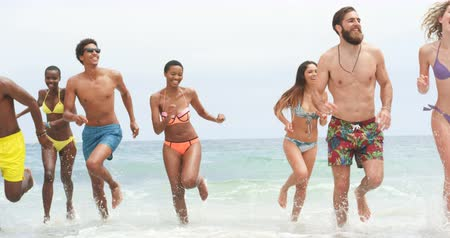 socialization : Group of mixed-race friends running together on the beach. They are having fun 4k Stock Footage