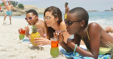 socialization : Side view of mixed-race female friends drinking cocktail drinks on the beach. They are relaxing on the beach 4k
