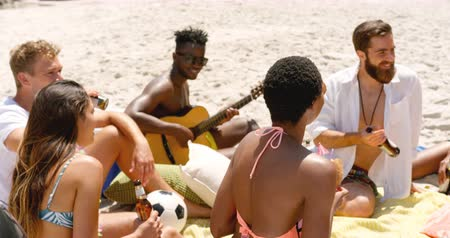 socialization : Group of mixed-race friends interacting with each other on the beach. They are drinking beer 4k